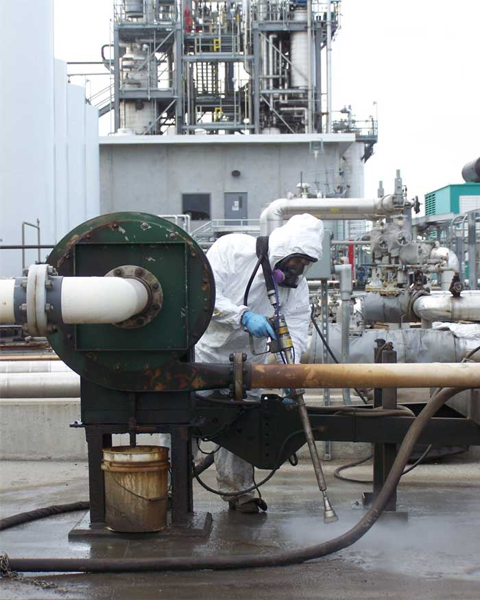 Photo of an iSi environmental professional power-washing and properly disposing of contaminants at a refinery as part of onsite facility support.