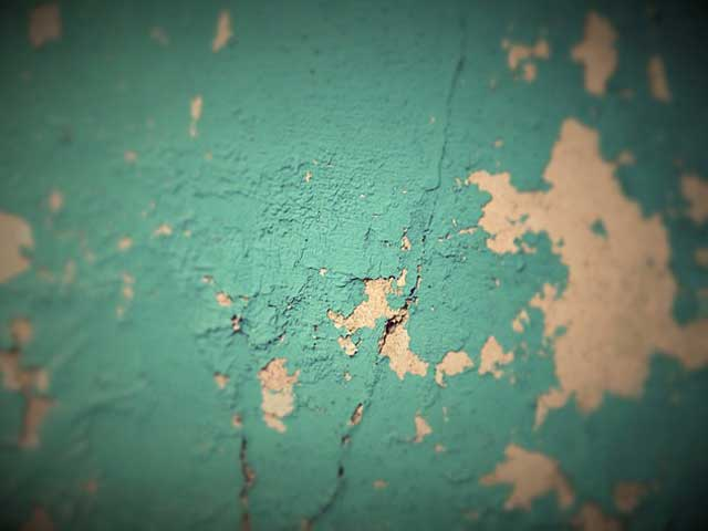 Photo of wall covered with peeling paint which iSi's lead abatement teams would remove.