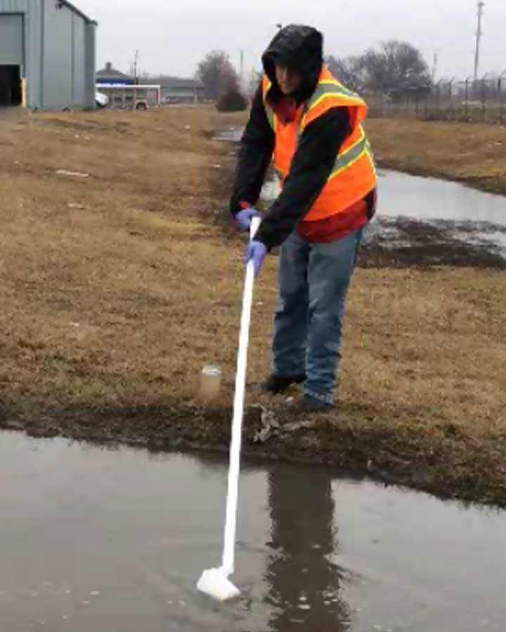 Photo of an experienced iSi technician using a water sampler to take a sample of stormwater for environmental compliance reporting.