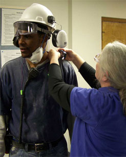 Photo of an iSi specialist using a noise dosimeter to measure a worker's noise exposure over a period of time for monitoring employee health.