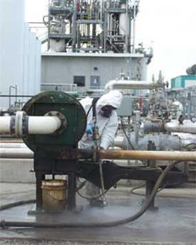 An iSi industrial cleaning technician powerwashes an area at an oil refinery.